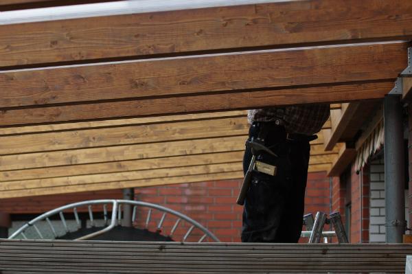 Die Balken an der Hauswand befestigen
