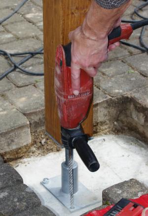 Die Holzpfosten im Fundament verankern
