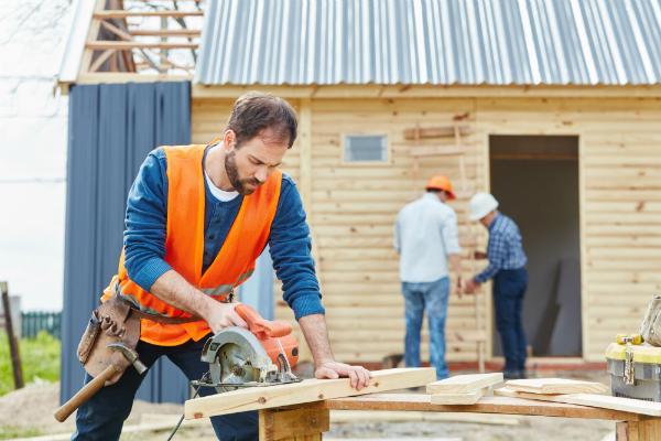 Handwerker mit Handkreissaege beim Hausbau