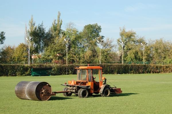 Traktor mit Schwermetallrasenrolle auf Fußballplatz