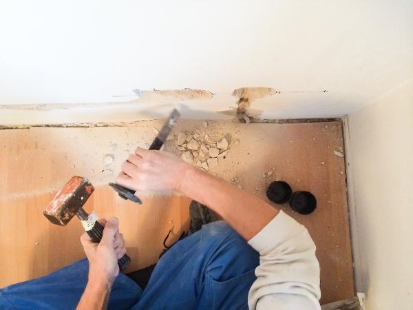Mit Hammer und Meissel Schlitz schlagen fuer neue Stromleitung und Steckdose