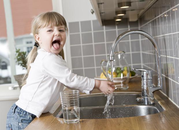 Kleines Mädchen freut sich über Wasser aus der Leitung