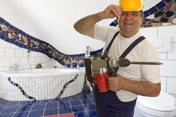 Handwerker mit mit Spezialbohrgerät - Fliesen bohren im Bad