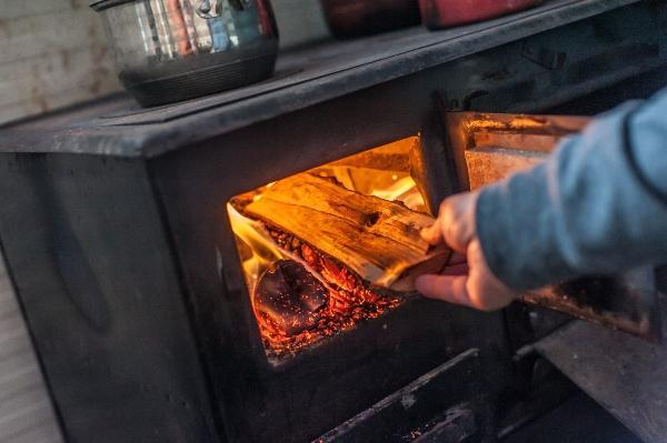 Mann legt Holz beim Holzherd nach