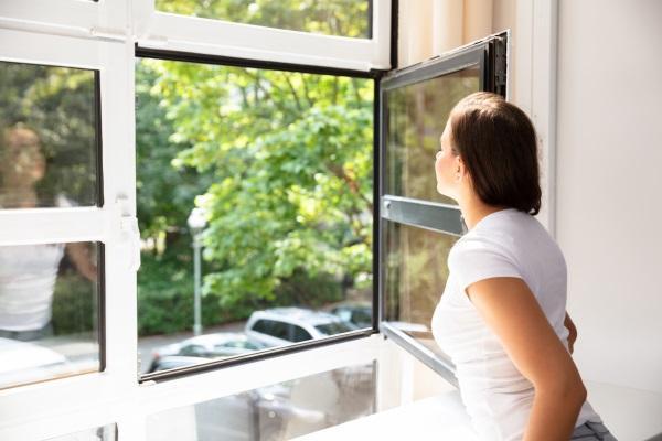 Eine Frau hat das Fenster ihrer Wohnung geöffnet und atmet die frische Luft ein Gegen stickige Luft