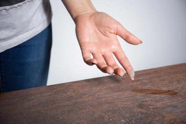 Eine Frau wischt mit dem Finger über eine staubige Tischplatte. An ihrem Finger haftet jede Menge Staub. Gegen stickige Luft
