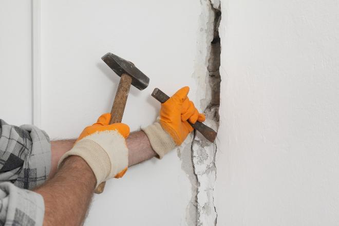 Mann meißelt eine Öffnung in eine Betonmauer