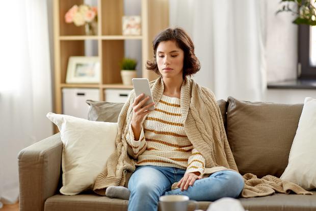 Frau sitzt auf Sofa mit Extra Strickpullover