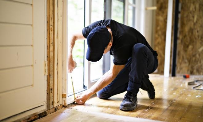 Mann misst Tür aus, um die Türbänder einzustellen