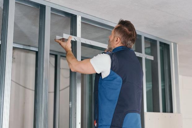 Mann installiert Ständerwerk aus Aluminiumprofilen für Trennwand im Zimmer