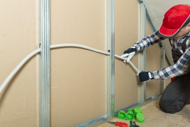 Mann verlegt Kabel in Trennwand