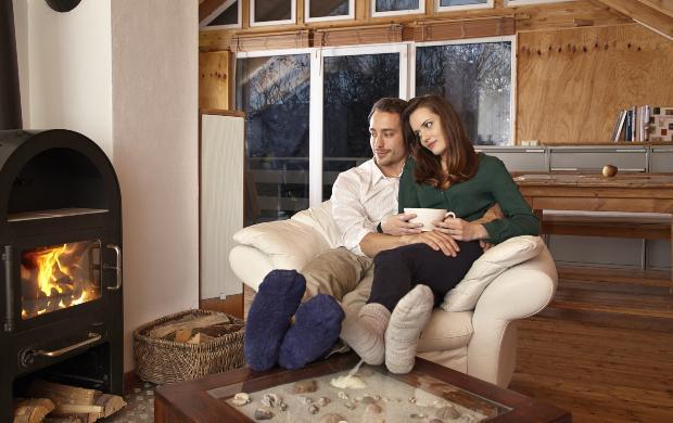 Junges Paar vor dem Kamin - Sicherheit am Kaminofen ist wichtig