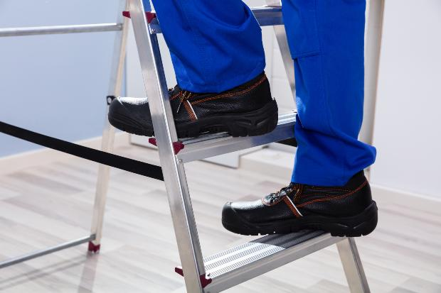 Mann auf Leiter - Arbeitsschuhe sorgen für Sicherheit