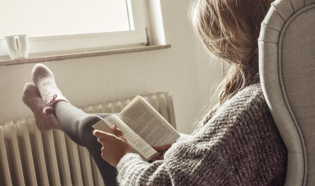 Frau liest Buch an der Heizung