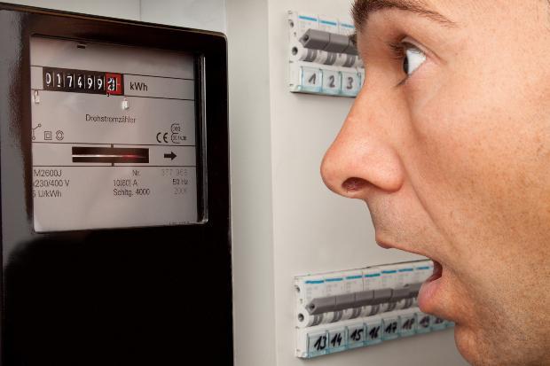 Mann schaut erschreckt auf Stromzähler