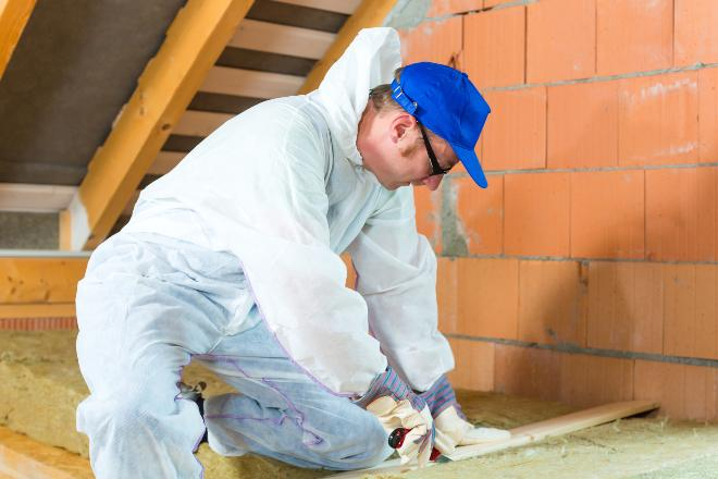 Mann schneidet Glaswolle auf dem Dachboden