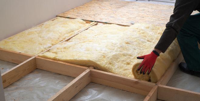 Mann legt Dämmwolle in ein Holzgerüst auf dem Dachboden