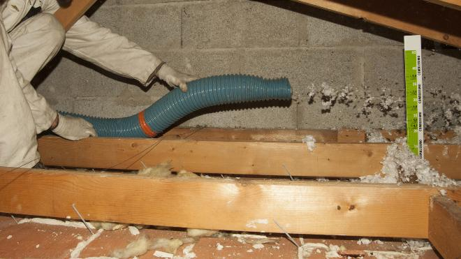 Mann nutzt Schlauch, um Dämmmaterial auf dem Dachboden zu verteilen