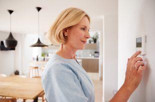 Frau am Thermostat - Funkregelung für Fußbodenheizungen