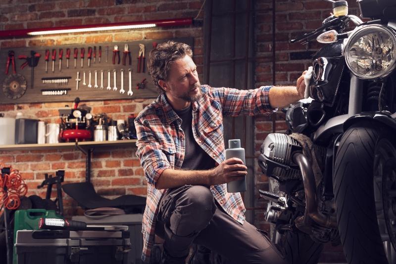 Mann poliert Motorrad in der Garage Garage als Werkstatt