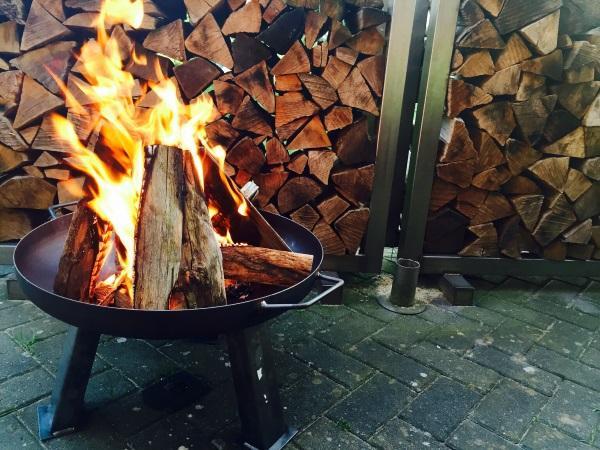 In einer feuerschale brennt ein Feuer. Im Hintergrund ist geschichtetes Holz zu sehen. Feuerschale zum Kochen und Grillen