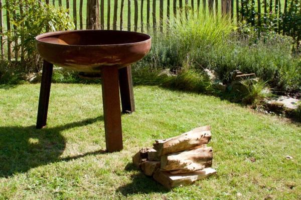Eine etwas angerostete Feuerschale ist einsatzbereit. Sie steht auf einer Grünfläche, davor liegt Feuerholz bereit. Feuerschale zum Kochen und Grillen