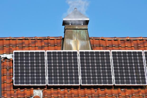 Ein rauchender Schornstein, vor dem eine Photovoltaikanlage zu sehen ist Wärmewende