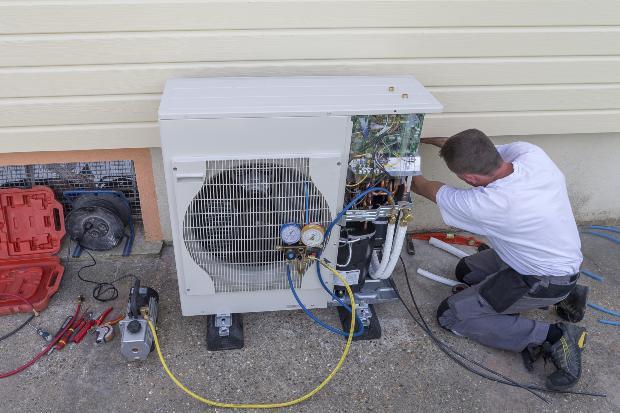 Ein Arbeiter ist damit beschäftig, eine Wärmepumpe zu installieren Wärmewende