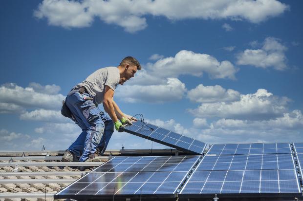 Zwei Arbeiter installieren eine Photovoltaikanlage auf einem Dach