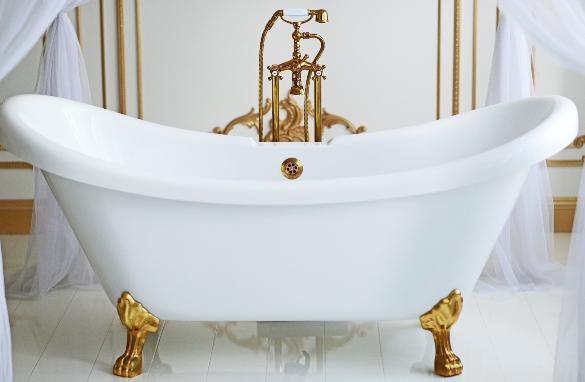 Eine altertümliche Badewanne mit vergoldeden Füßen und Armaturen Stahlemaille im Badezimmer