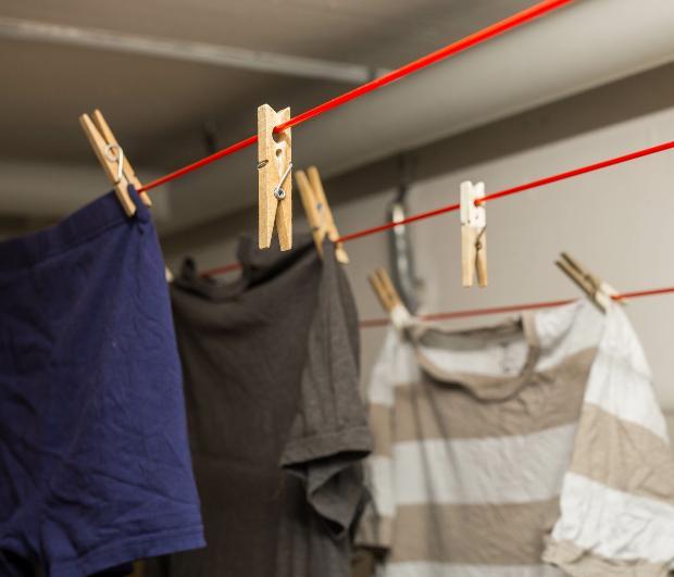In der Waschküche im Keller sind mehrere Kleidungsstücke zum Trocknen aufgehängt Kellerlüfter gegen Feuchtigkeit