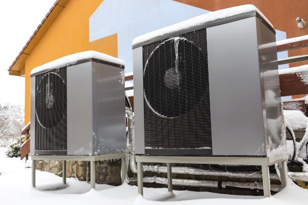 Zwei Wärmepumpen sind vor einem Haus installiert, es liegt Schnee