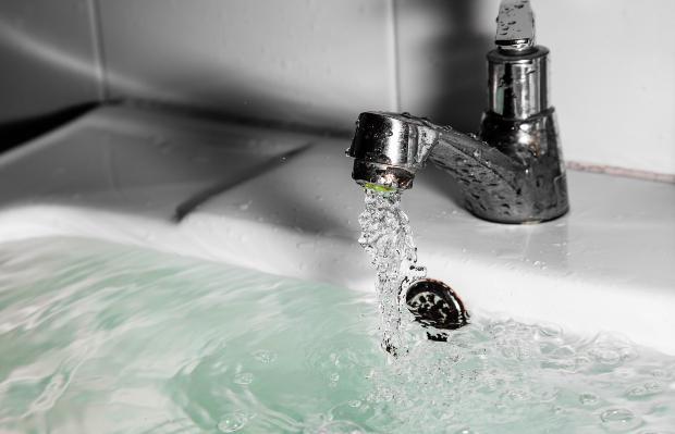 Ein Waschbecken ist bis zum Rand mit Wasser gefüllt Abfluss am Waschbecken wechseln