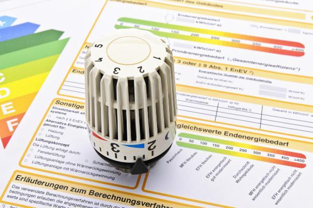 Ein Thermostat liegt auf einem Formular zur Heizungsförderung