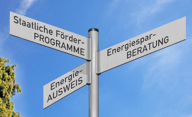 """Ein Symbolbild zeigt einen Wegweiser mit den Schildaufschriften: """"Staatliche Förderprogramme"""", """"Energiesparberatung"""" und """"Energieausweis"""" Förderung bei der Heizungsumstellung"""