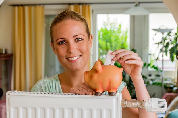 Eine Frau steckt einen Geldschein in ein Sparschwein, das auf einer Heizung steht Förderung bei der Heizungsumstellung
