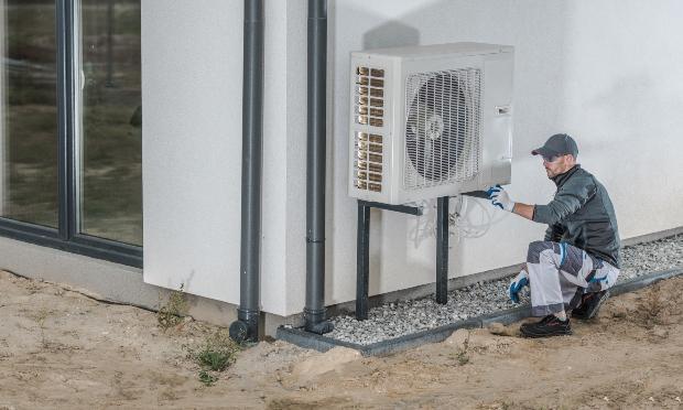 Ein Arbeiter montiert eine Wärmepumpe