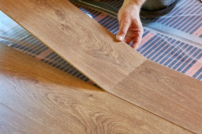Mann legt Laminat auf Fußbodenheizung - Wandheizung oder Fußbodenheizung bieten jeweils eigene Vorteile