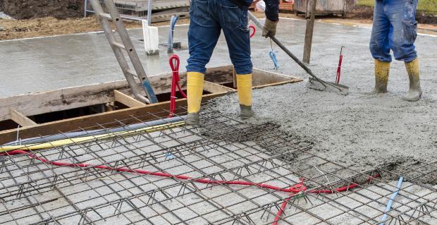 Männer legen Fundament für Hausbau - Blitzschutz und Erdung anschaulich