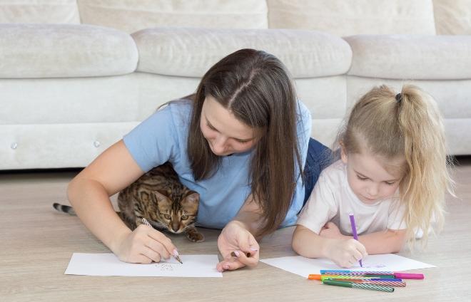Mutter mit Katze und Kind malen auf dem Boden liegend