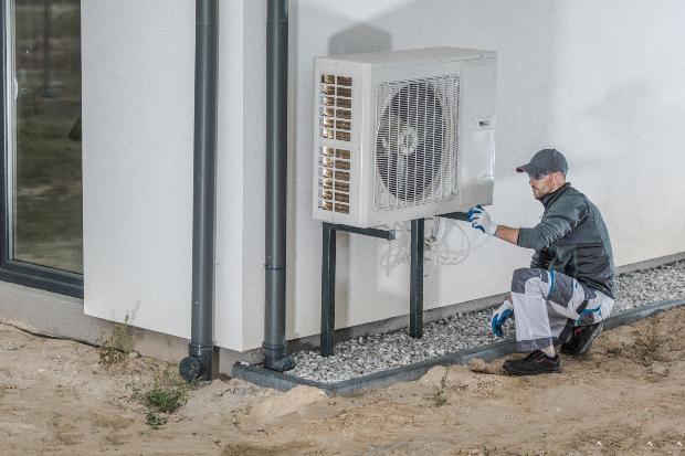 Ein Handwerker bei der Montage einer Wärmepumpe