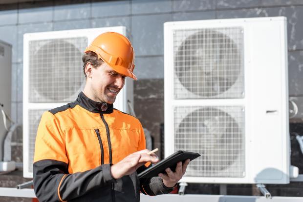 Ein Handwerker überprüft routinemäßig eine Wärmepumpe