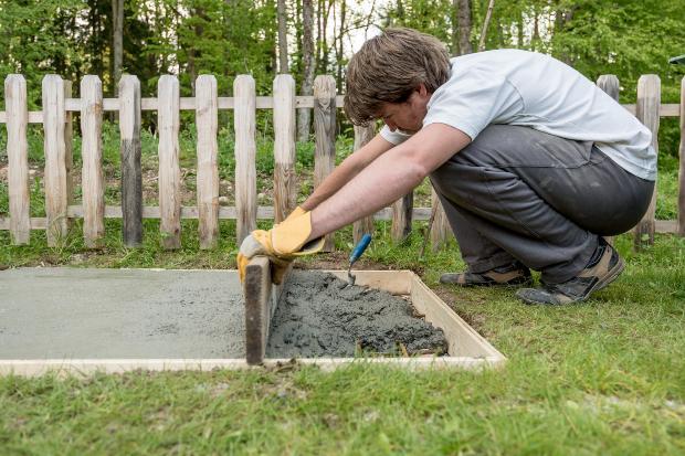 Mann baut Fundament im Garten - Geräteschuppen einrichten