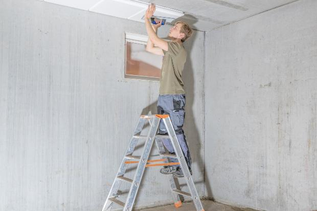 Mann installiert Dämmung an Kellerdecke - Tipps für den Kellerausbau