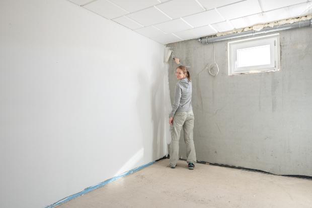 Frau streicht Kellerwand in weißer Farbe