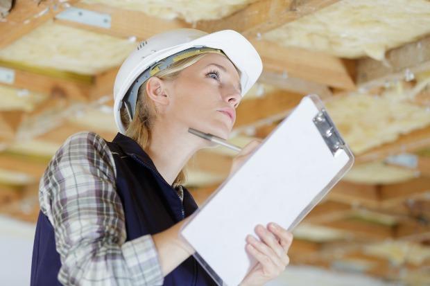 Junge Frau mit Schreibunterlagen begutachtet einen Dachboden