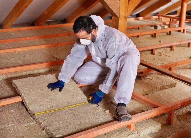 Mann verlegt Dämmmaterial auf Dachboden - ein wesentlicher Schritt beim Dachausbau