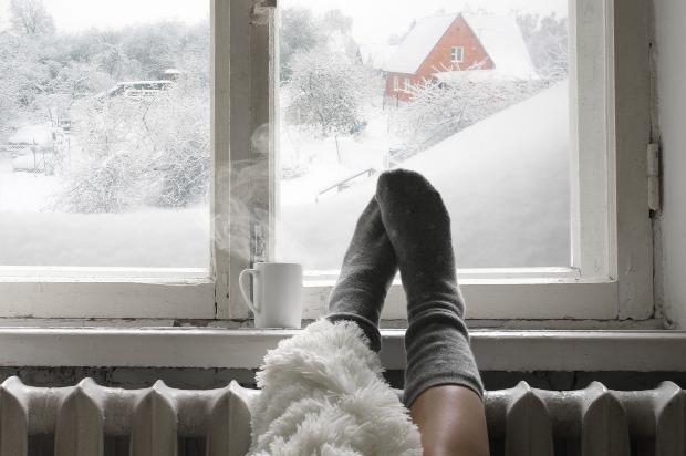 Jemand legt im Winter seine Füße auf die Heizung vor dem Fenster