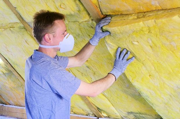 Mann dämmt Dachboden - durch Dämmung Energiekosten sparen