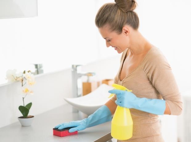 Frau reinigt Badezimmer - Staub dort in der Regel nicht so stark